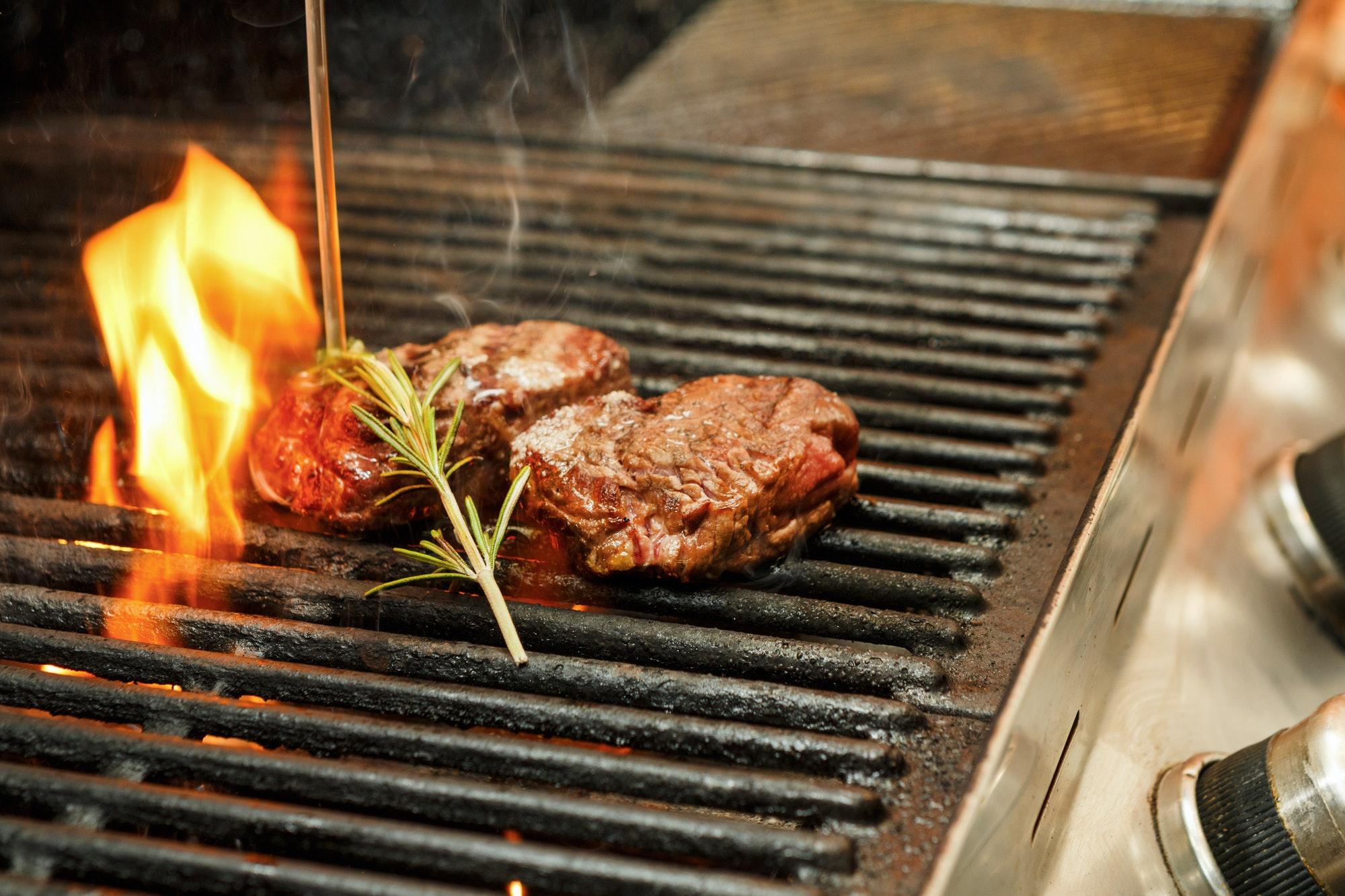 Meat steaks on grill on open fire